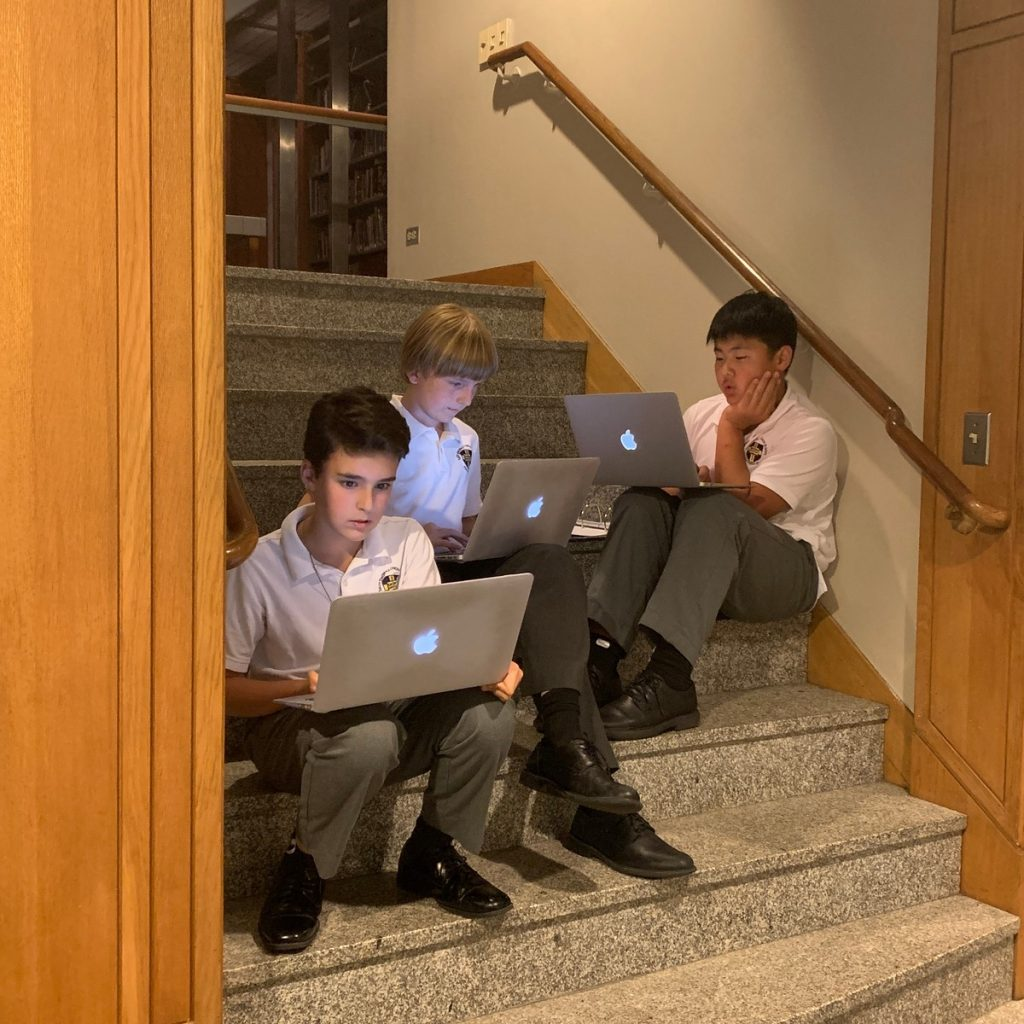 Saint Thomas Chori School students using laptops on a stairwell