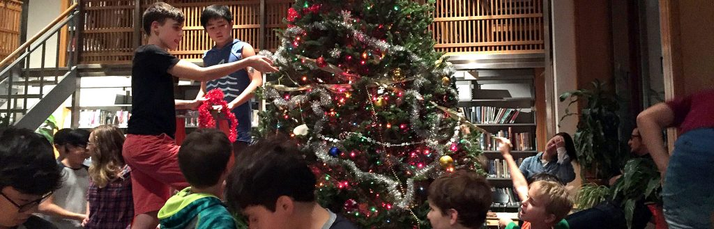 Saint Thomas Choir School students trimming a Christmas tree in the library
